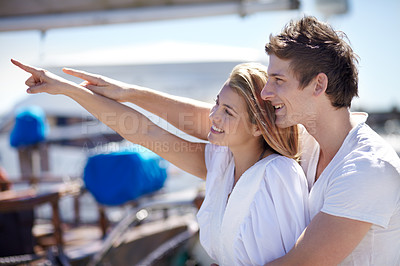 Buy stock photo Young couple pointing away while at the marina