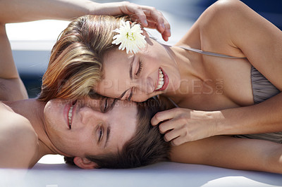 Buy stock photo Loving young couple lying in the sunshine together