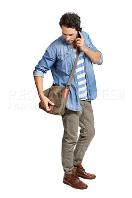 Buy stock photo A handsome young man looking for something in his sling bag while talking on his phone