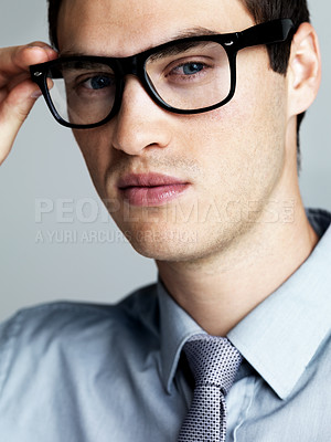 Buy stock photo Portrait of a handsome young business executive wearing glasses against a grey background