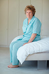 Mature woman sitting on a bed