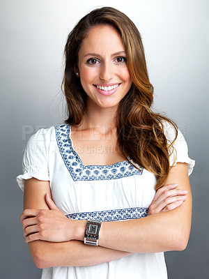 Buy stock photo Portrait of a beautiful young woman standing with folded hand against grey background