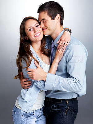 Buy stock photo Portrait of a beautiful young couple hugging each other against grey background