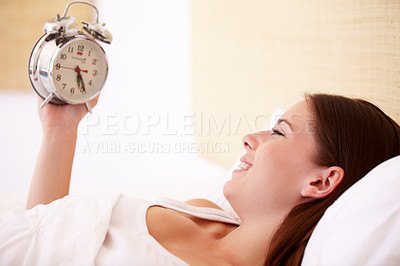 Buy stock photo A gorgeous young woman smiling while looking at her alarm clock