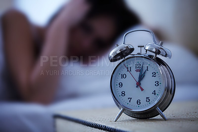 Buy stock photo A young woman covering her ears as her alarm goes off