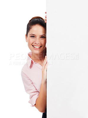 Buy stock photo Portrait of a young woman looking at the camera from behind a large blank placard isolated on white