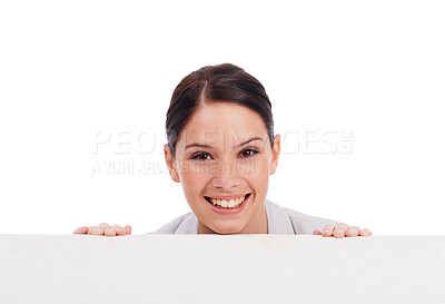 Buy stock photo Shot of a young woman looking over a blank placard at the camera isolated on white