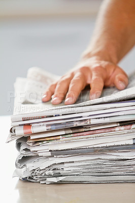 Buy stock photo Shot of a hand on top of a stack of newspapers