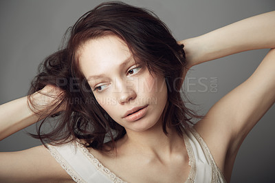 Buy stock photo A beautiful young woman posing with hands in her hair