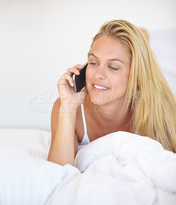 Buy stock photo A gorgeous young woman talking on the phone while lying in bed