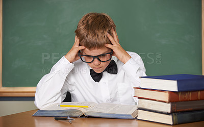 Buy stock photo An overwhelmed schoolboy in a bow-tie and glasses sitting with his hands in his hair
