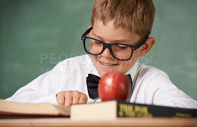 Buy stock photo A young boy wearing glasses and a bow-tie concentrating on his reading and smiling