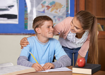 Buy stock photo A supportive young teacher leaning over her student while he writes in a book