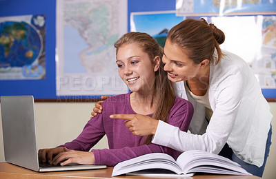 Buy stock photo A teacher leaning over her pupil and pointing to something on her laptop screen