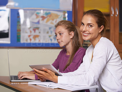 Buy stock photo A young teacher helping her student with a project on her laptop while smiling at the camera