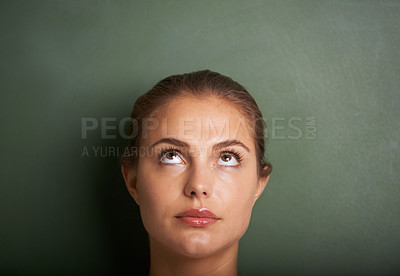 Buy stock photo Closeup of a young woman standing in front of a blackboard looking up