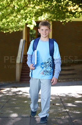 Buy stock photo A smiling young boy wearing a backpack on his way to school