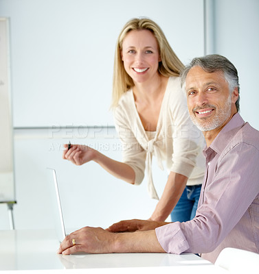 Buy stock photo Portrait of two mature designers working on a laptop and smiling at the camera