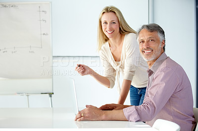 Buy stock photo Two smiling coworkers discussing business in a meeting using a flip chart and laptop - Portrait