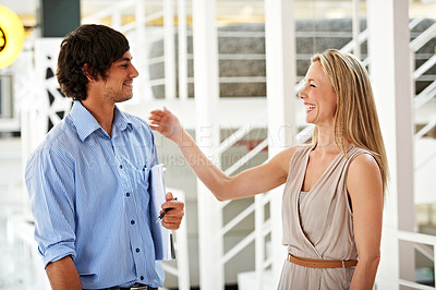 Buy stock photo A pretty businesswoman congratulating a colleague with a pat on the shoulder