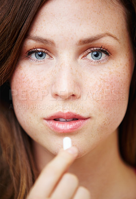 Buy stock photo Portrait of an attractive young woman taking some medication