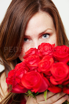 Buy stock photo Portrait of an attractive young woman peering over a bouquet of roses