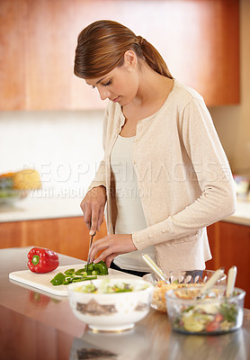 Buy stock photo An attractive young woman cooking in the kitchen