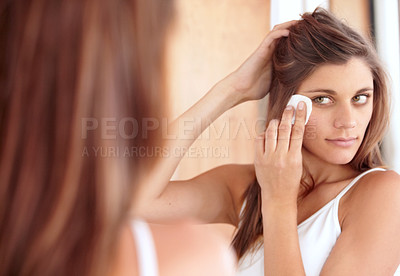 Buy stock photo A beautiful young woman wiping the make-up off her face