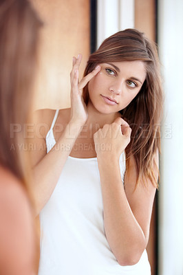 Buy stock photo A beautiful young woman applying cream to her face