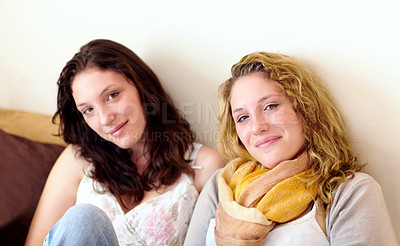 Buy stock photo Portrait of two sisters sitting on a sofa at home