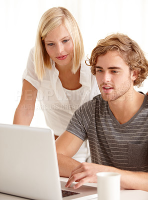 Buy stock photo A handsome young man showing his girlfriend something on his laptop