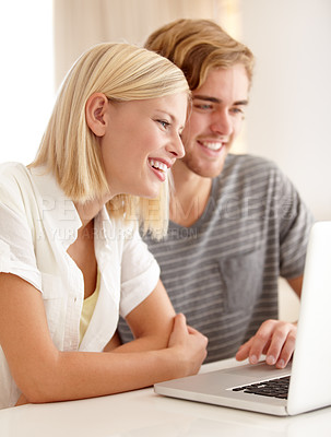 Buy stock photo A happy young couple using a laptop to browse the web