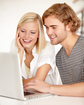 Buy stock photo A young couple using a laptop to surf the net