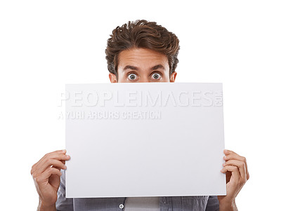 Buy stock photo Portrait of a handsome young man peering over a sign for your copyspace