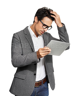 Buy stock photo A handsome young man looking worryingly at his tablet