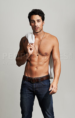 Buy stock photo Profile of a handsome young man standing with his shirt over his shoulder
