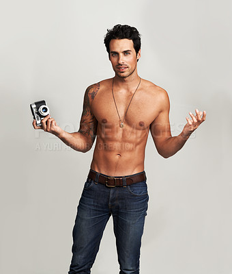 Buy stock photo Portrait of a shirtless young man gesturing while holding a camera