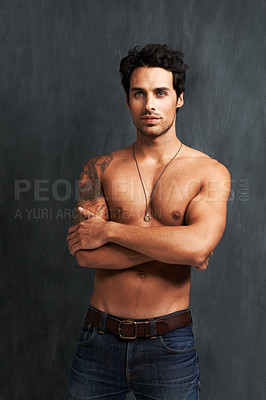 Buy stock photo A shirtless young man standing with his arms folded
