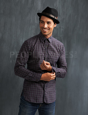 Buy stock photo A hip young man buttoning his shirt cuffs