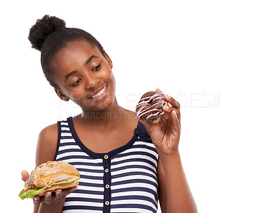 Buy stock photo Studio shot of a young african american girl trying to choose between eating a donut or a sandwich