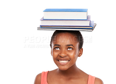 Buy stock photo Studio shot of a young african girl balancing books on her head isolated on white