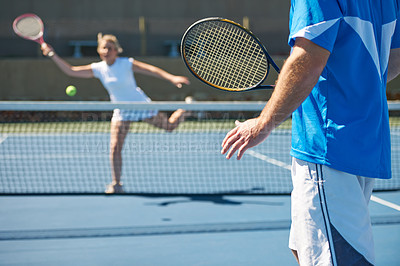 Buy stock photo A talented young tennis player returning her male opponents shot