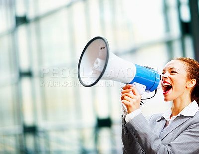Buy stock photo Happy young African American business woman screaming into a megaphone