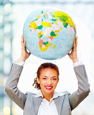 Buy stock photo Portrait of a happy African American business woman holding a globe above her head