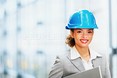 Buy stock photo Portrait of a cute young business woman with a hardhat holding a laptop