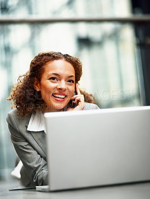 Buy stock photo Young African American business woman using a laptop on the floor, speaking on the cellphone