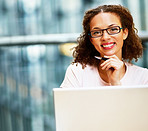 Happy young business woman wearing spectacles working on a laptop