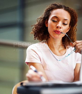 Buy stock photo Pretty African American business woman making a note in her files