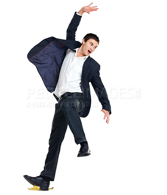 Buy stock photo Portrait of a handsome young business man slipping on a banana peel against white background