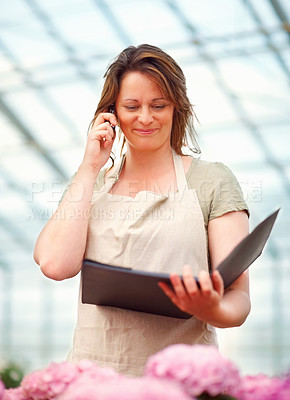 Buy stock photo Pretty young woman speaking on the mobile while at the florist